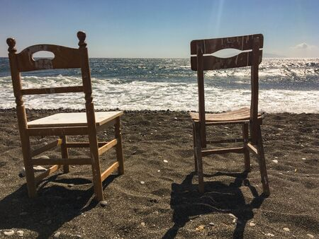 Two old wooden chairs on a beach at Kamari in Santorini, Greece. On the shore of the Aegean Sea, in front of sun and sea waves.