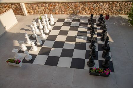 Mega chessboard in Santorini, Greece, in the traditional colors of the island, the black of the lava and the white of the houses. Town of Kamari by the Aegean sea.