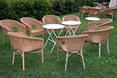 Armchairs with outdoor tables on a green lawn for restaurants or bars. Typical for breakfast or coffee break in Italy.