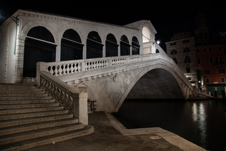 Night photo Rialto Bridge in Venice, Italy. Overview of the white marble bridge illuminated by reflections on the water of the Grand Canal.