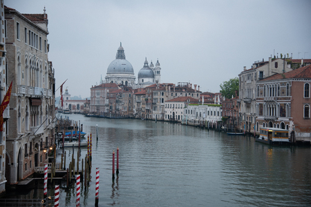 Grand Canal and the island of Santa Maria della Salute with the Customs from the Bridge Academy in Venice, Italy. Widespread dawn light over the lake with a view of the houses and the ferry stop.