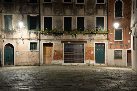 Night photography of typical houses with doors and windows in Venice, Italy. Magical atmosphere of lights at night.