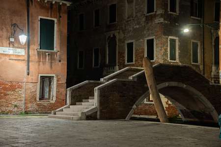 Night photograph of the Ruga Old bridge in the Campo San Giacomo of the Orio in the Santa Croce district in Venice, Italy. Typical old Venetian houses with facade on the bridge and canal.