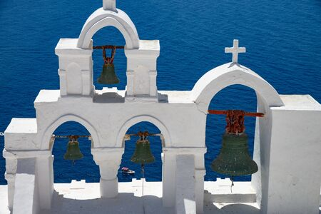 Bell tower of Oia in Santorini Greek island.Classic bell tower with bells. View of the caldera gulf.