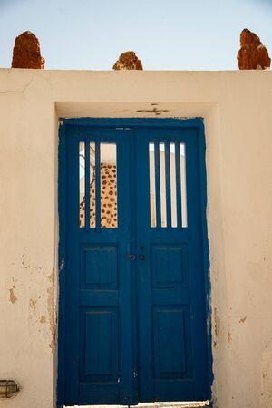 Green door in Oia, Santorini island, Greece. Characteristic entrance in vintage colored wood.