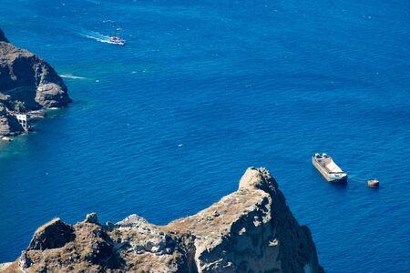 Gulf of caldera seen from Fira, on Santorini island in Greece. Panorama of the Aegean Sea, with boats. Stock fotó