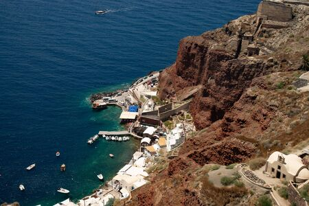 Gulf of caldera with the small port of Ammoudi, in Santorini, island of the Aegean Sea in Greece. Panorama of the cliff of volcanic rocks of Oia.