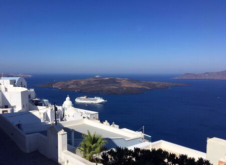 Typical houses of Oia in Santorini volcanic island of the Aegean Sea in Greece. A caldera gulf and view of the island with the volcano of Nea Kameni.