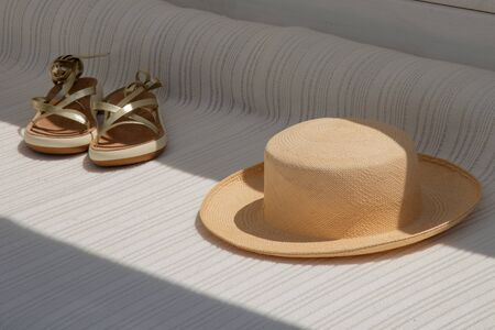 Fashionable womens hat and sandals. Outdoors with sun and shade on white armchair with stripes.