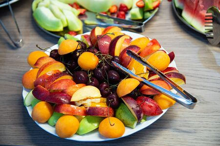 Plate with fresh fruit ready for morning breakfast. Cherries, pears, apricots, peaches.
