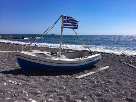 Small boat with Greek flag. Beach of Monolithos island of Santorini, Greece. Stock fotó - 132055072