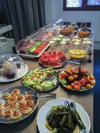 Table with fruit and vegetables and pastries prepared for a rich breakfast. Colorful fresh fruit with yogout, cakes and cold cuts. Stock fotó - 132054928