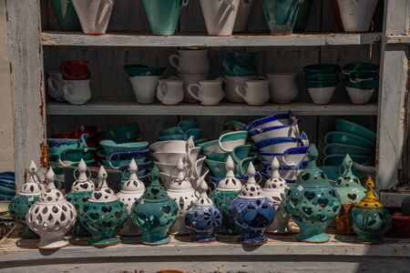 Greek souvenirs from the island of Santorini in the Aegean Sea. Lamps, ceramic jars in the traditional Greek style. Exposed in an old trumeau in the city of Oia on the island of Santorini, Greece.