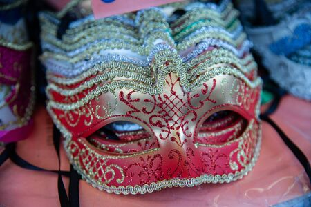 Group of carnival masks during the Mardi Gras fashion shows. Isolated colored on a counter for sale. Masks that cover the face on the eyes.