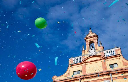 Piazza del Guercino in Cento, Ferrara, Italy, during the famous carnival. Against the blue sky, throwing confetti, balloons, life jackets.