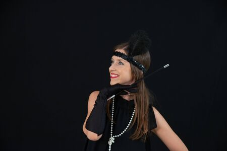 Smiling girl in charleston black dress, with cigarette in the mouthpiece, white pearls necklace and headband on the hats with feather. Lady with vintage dress in 20s style on a black background. Stock fotó - 133372274