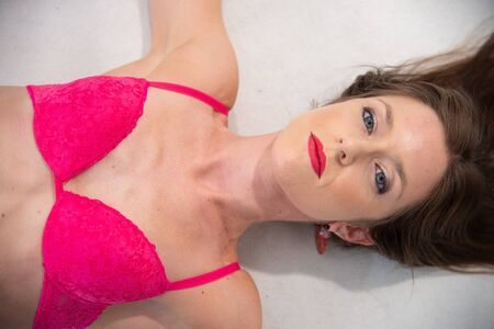 Closeup of girl with brown hair over her head with blue eyes, lying down, in red bra. Detail of girl looking in sexy room photo on white background. Stock fotó - 133372277