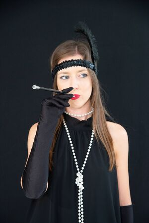 Smiling girl in charleston black dress, with cigarette in the mouthpiece, white pearls necklace and headband on the hats with feather. Lady with vintage dress in 20s style on a black background.