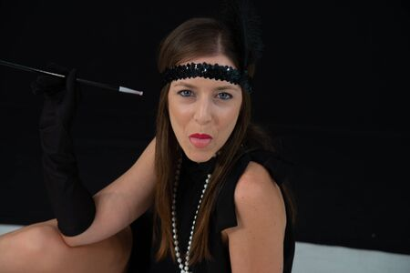 Girl showing her tongue, in black charleston dress, with cigarette in the mouthpiece, in white pearls and band on the hats with feather. Lady with vintage dress in a 20s style