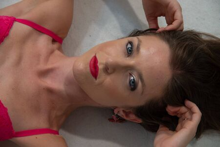 Closeup of girl with brown hair over her head with blue eyes, lying down, in red bra. Detail of girl looking in sexy room photo on white background. Archivio Fotografico - 133372332