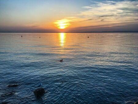 Colorful sky in a beautiful evening view of the lake. Lake Garda, Verona, Italy with setting sun. Stock fotó - 133372337