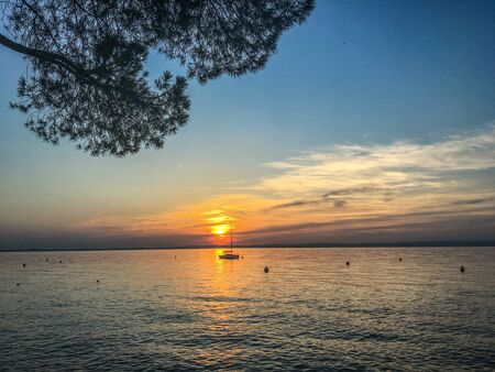 Colorful sky in a beautiful evening view of the lake. Lake Garda, Verona, Italy with setting sun.