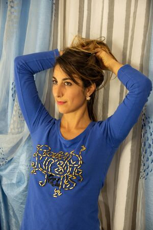 Close-up of an attractive young woman. He is wearing a blue pajama shirt with designs. Background of white and blue curtains. Stock fotó - 134978064