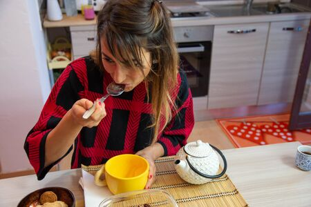 Young brunette woman smiling while having breakfast in the morning. Wear a black and red checkered shirt. Red color background, copy space. Stock fotó