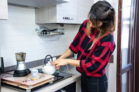 Young brunette woman preparing morning breakfast, smiling as she pours coffee into the cup with a