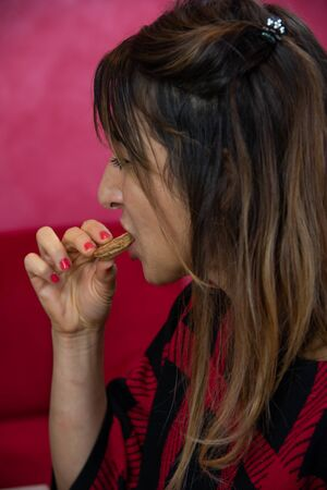 Closeup of young woman in brunette profile while eating biscuit for morning breakfast. He is wearing a black and red checkered shirt, a red background.
