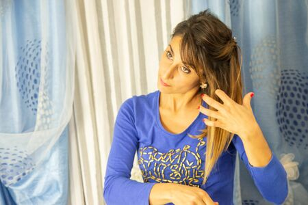 Close-up of an attractive young woman. He is wearing a blue pajama shirt with designs. Background of white and blue curtains. Stock fotó - 134977781