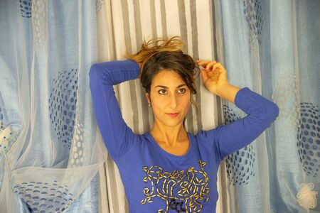 Close-up of an attractive young woman. He is wearing a blue pajama shirt with designs. Background of white and blue curtains. Stock fotó - 134977772