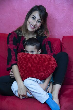 The young mother hugs her son in a big red stuffed heart. Mother love concept. Stock fotó