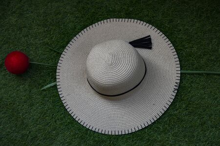 Summer hat for women of the fisherman type in white cotton. Photo with green artificial lawn and fake red flower background. Stock fotó