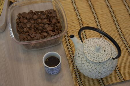 Breakfast cereal muesli with two cups with coffee, teapot, bread and jar of honey.