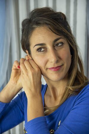 Close-up of an attractive young woman. He is wearing a blue pajama shirt with designs. Background of white and blue curtains.