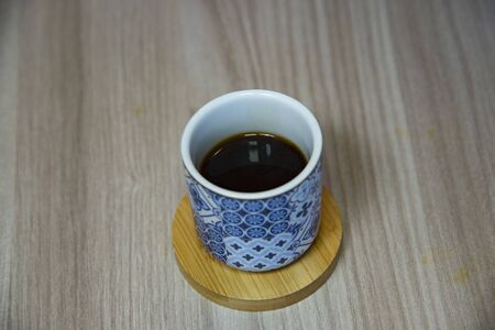 Cup without handle with coffee with light blue patterns. On wooden saucer above table. Stock fotó