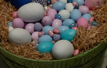Basket with multicolored Easter eggs of different sizes.