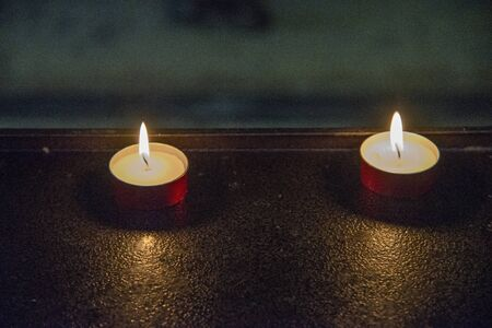 Close up of two votive candles in a church. Candles in the dark with flames on red copper supports. Stock fotó