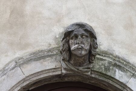 Human face figure as the keystone of an entrance arch to a house. Stone worked said ashlar in Vicenza, Italy.