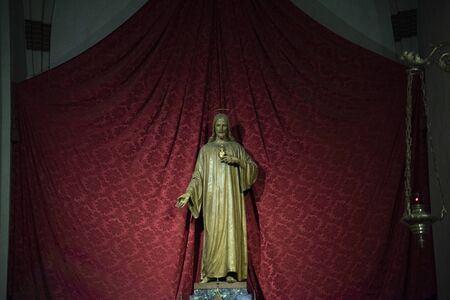 Golden Christ statue in the church of Santa Maria in Foro called Dei Servi in Vicenza, Italy. Red curtain background.