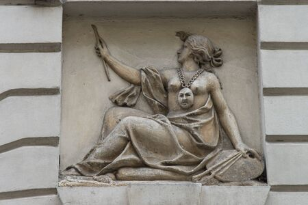Figure of a woman representing the arts as a bas-relief sculpture of an entrance in a building in Padua, Italy.