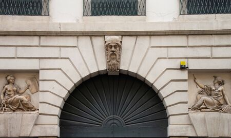 Bas-relief sculpture of an entrance in a building in Padua, Italy. You represent two women who represent the arts and the figure of the human face with the beard as the keystone.