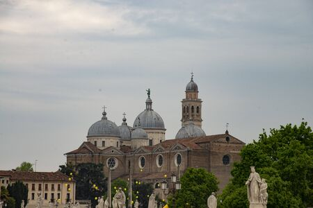 The abbey basilica of Santa Giustina is an important Catholic place of worship in Padua. View of the multiple external domes. From the Prato della Valle square yellow balloons fly.