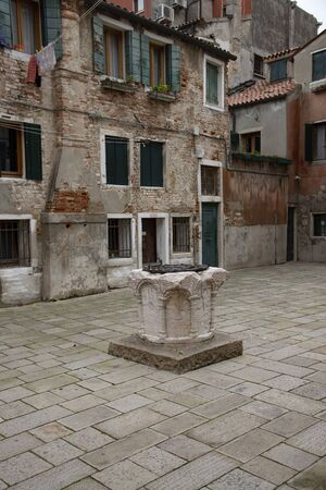 Characteristic square with old well for rainwater called calle in Venice, Italy.