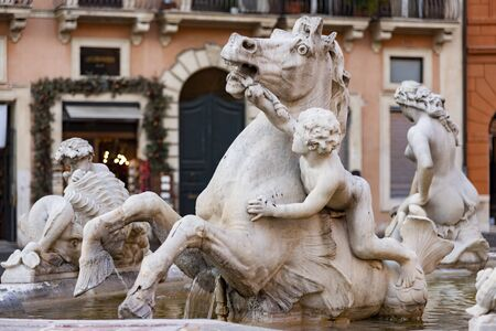 The Fontana del Nettuno, also called the Fontana dei Calderari, is the fountain located in Piazza Navona, Rome, Italy. Detail of the Nereids group of sea horses led by children in white Carrara marble