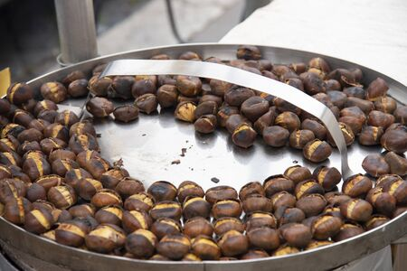 Close up of roasted chestnuts for sale on the street. Traditional street food in the winter. Stock fotó