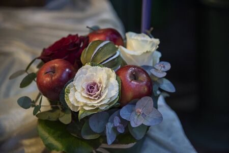 Centerpiece composition of flowers with roses, ornamental cabbage, apples and green leaves.