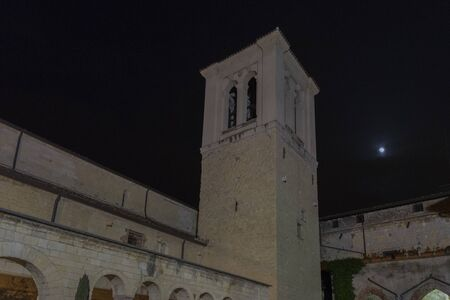 Night photo of the church of San Giovanni in Valle in Verona, Italy. Detail of the square bell tower with the moon in the background. Stock fotó