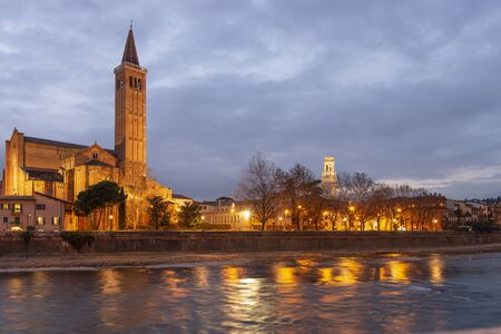 Night photo along the Adige river, Verona, Italy. Basilica of Santa Anastasia with the bell tower of the cathedral.
